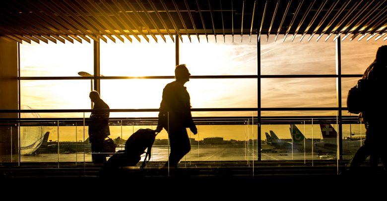 silhouettes of passengers against an airport at sunrise
